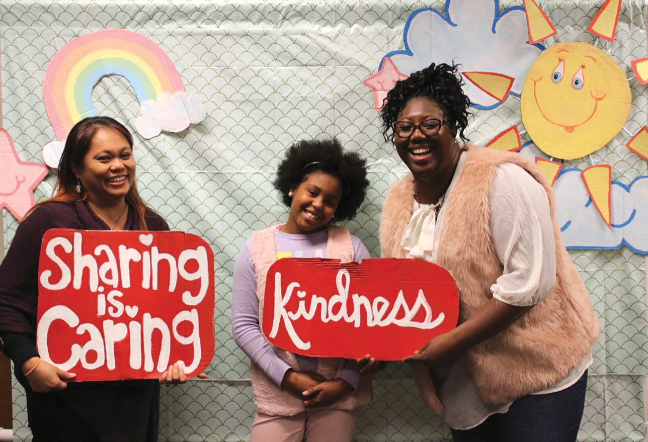 "Lai-Lani Ovalles, Alaia Greer, and Amanda Greer hold handmade signs reading ""sharing is caring"" and ""kindness"""