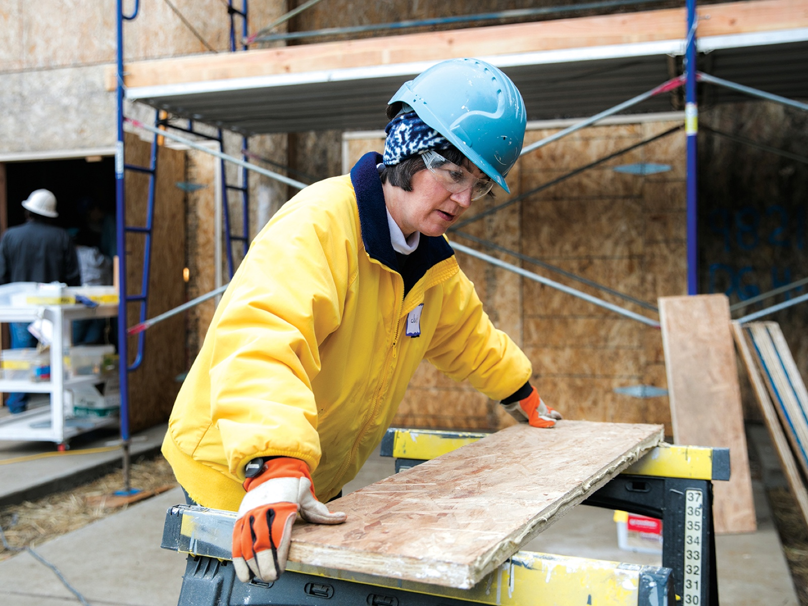 Julie Christiansen placing lumber on a sawhorse at a construction site