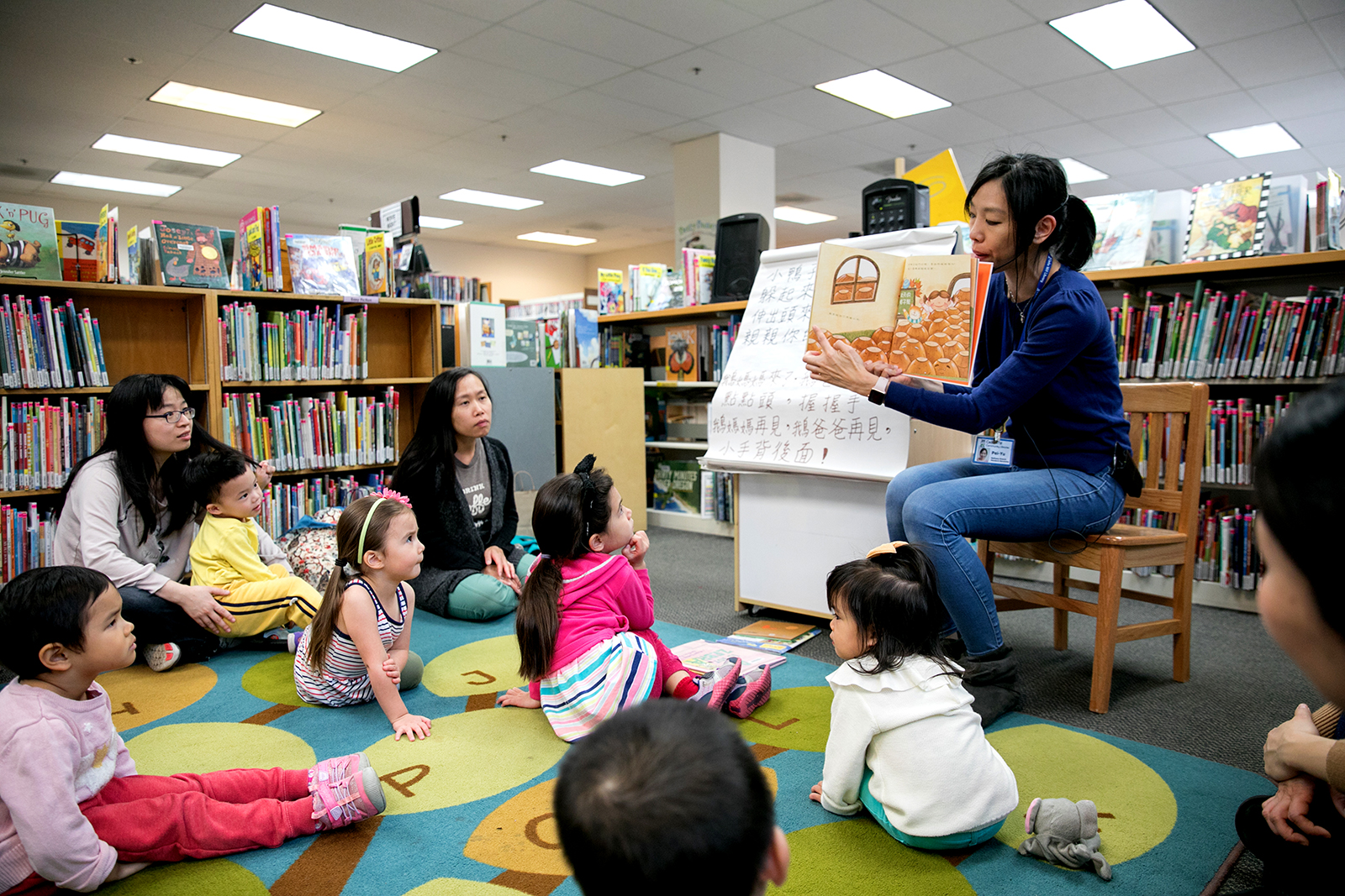 Instructor reading to children and parents for Mandarin Story Time